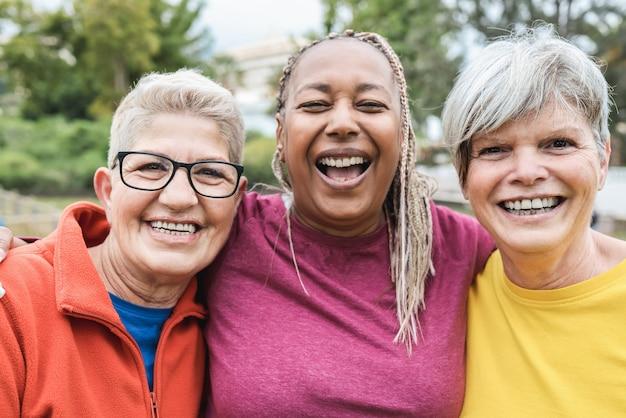 屋外でのスポーツトレーニングの後に一緒に楽しんでいる多民族の年配の女性-右の女性の顔に焦点を当てる