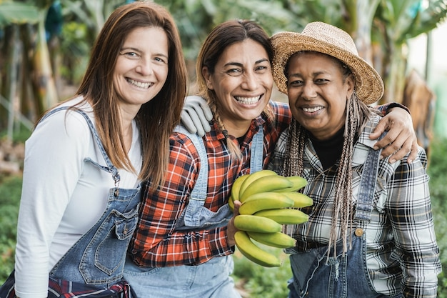 Multiracial senior women working at garden while holding a banana bunch - main focus on center woman face