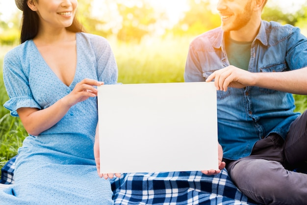 Multiracial smiling couple with blank paper sitting