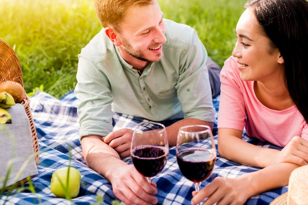 Multiracial smiling enamored couple lying on checkered plaid on picnic