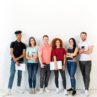 Multiracial smiling group of people standing in front of white background looking at camera holding paper and electronic gadget