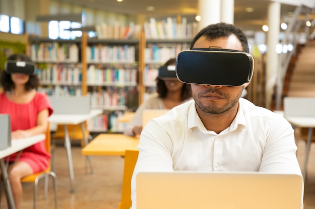 Multiracial students using vr glasses for work in class