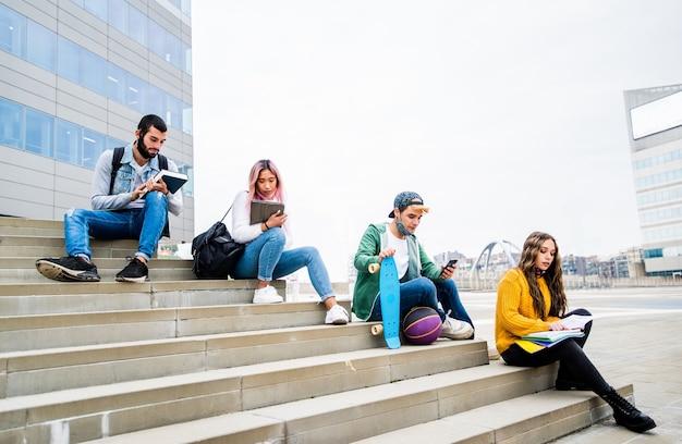 大学のキャンパスに座って勉強しているフェイスマスクを持つ多民族の学生-若い学生が屋外で一緒に楽しんでいる新しい通常のライフスタイルの概念。