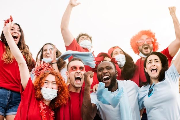 チームをサポートしながら叫んで保護フェイスマスクを身に着けている多民族のサポーター