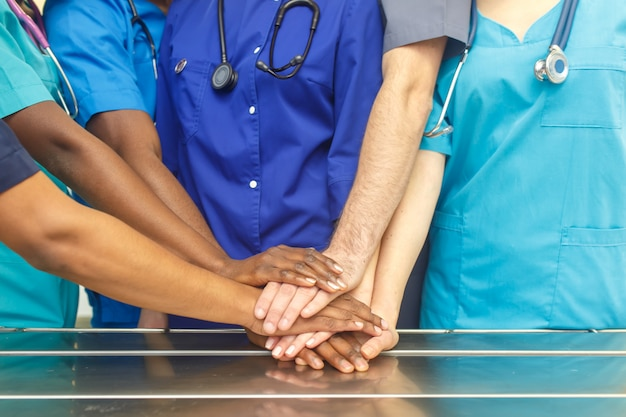 Многорасовая команда молодых врачей, укладка руки в помещении. группа многорасовых доктор хирургии команды укладки рук в операционной