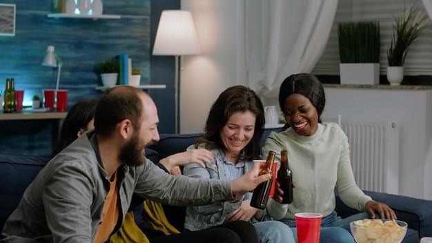 Многонациональная команда смотрит комедийный сериал, сидя на диване поздно ночью в гостиной. взволнованные друзья едят закуски, пьют пиво со смешной реакцией, вместе проводят ночь