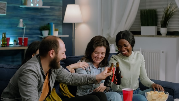 Multiracial team watching comedy movie series while sitting on sofa late at night in living room. excited friends eating snacks, drinking beer having funny reaction, enjoying night together