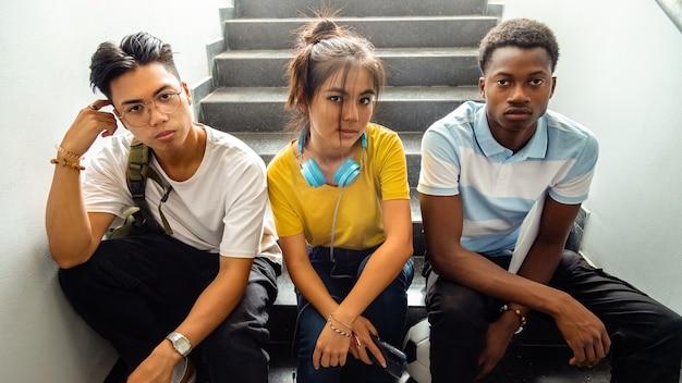 Многонациональные подростковые старшеклассники сидят на лестнице и смотрят в камеру баннер снова в школу