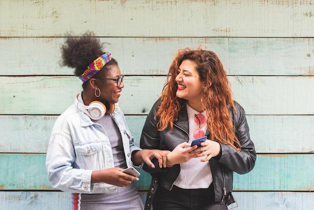 Multiracial teenager girls using mobile phone outdoors