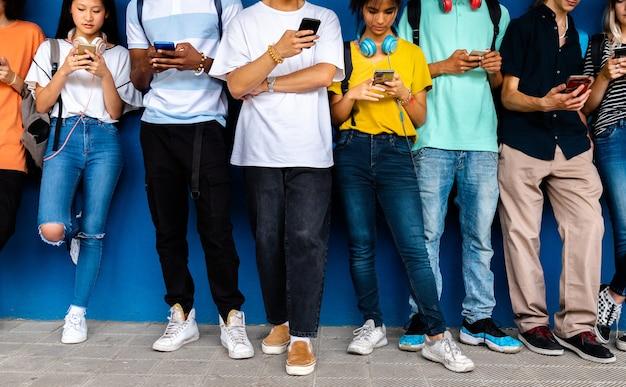 다인종 십대들은 서로를 무시하고 휴대폰을 보고 있습니다. 소셜 미디어 중독 개념입니다.