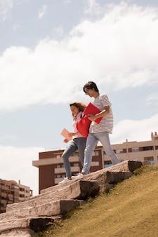 Multiracial teenagers walking down stairs