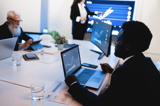 Команда многорасовых трейдеров проводит анализ фондового рынка в офисе хедж-фонда - в центре внимания лицо африканского человека
