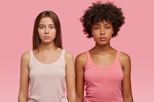 Donne multirazziali in gilet casual, stanno seriamente in piedi l'una accanto all'altra contro il muro rosa, andando ad allenarsi insieme.