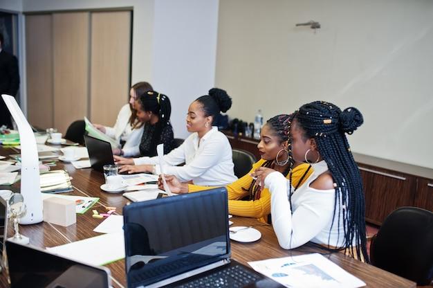 多民族の女性の同僚、オフィスの多様性の女性パートナーの乗組員がテーブルに座っています。