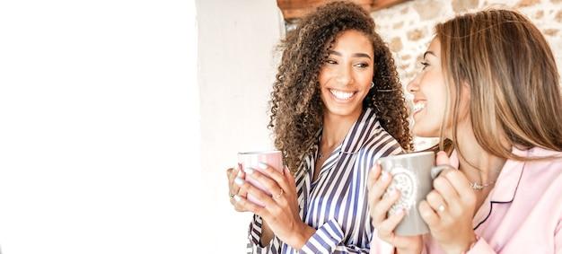 パジャマで茶碗を持ってお互いを見つめている多民族の女性カップルが目覚めた。ゲイの家族