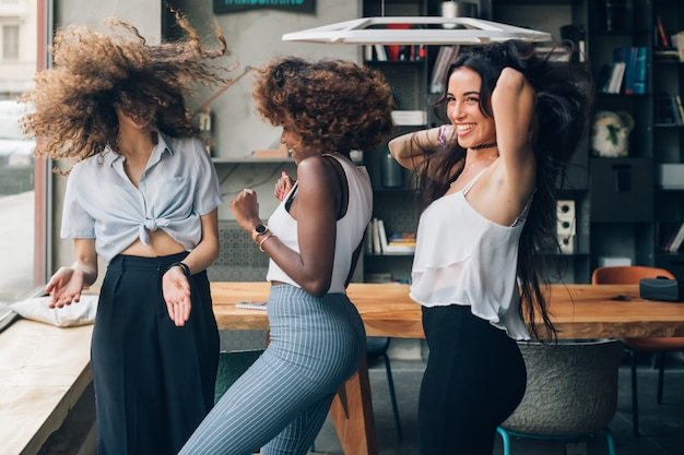 Multiracial women dancing in modern loft