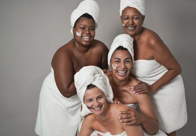 一緒に美容の日をしている多民族の女性-スキンケア治療をしている多世代の人々