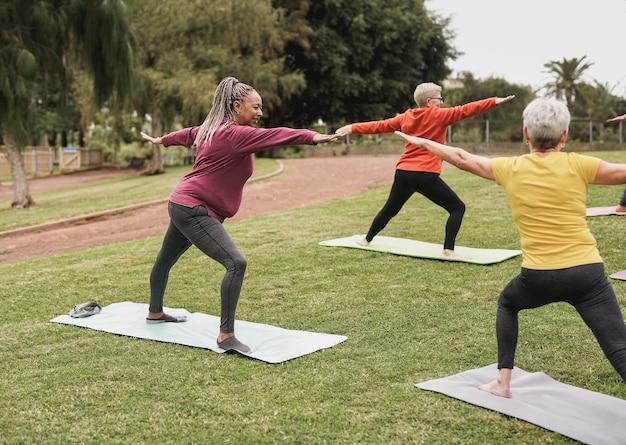 都市公園でコロナウイルスの発生のために社会的な距離でヨガの練習をしている多民族の女性-健康的なライフスタイルとスポーツの概念