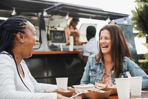 야외 푸드 트럭 레스토랑에서 식사하는 다인종 여성 - 아프리카 여성의 얼굴에 초점