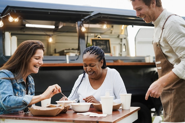 야외 푸드트럭 레스토랑에서 식사하는 다인종 여성 - 여름과 우정 개념 - 아프리카계 미국인 여성의 얼굴에 초점