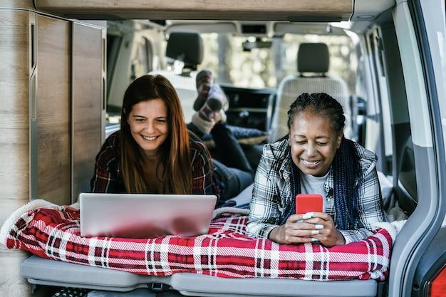 コンピューターのラップトップで作業し、コーヒーを飲みながらキャンピングカーの中でキャンプを楽しんでいる多民族の女性の友人-シニアアフリカの女性の顔に焦点を当てる