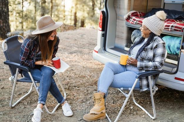 屋外でコーヒーを飲みながらキャンピングカーでキャンプを楽しんでいる多民族の女性の友人-シニアアフリカの女性の顔に焦点を当てる