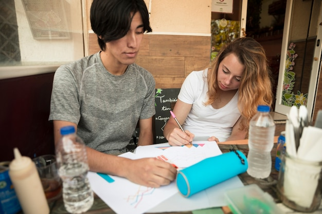 Multiracial young couple painting papers on table