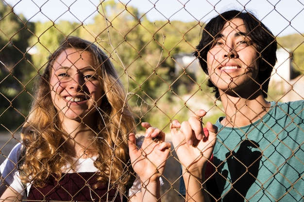 Multiracial young couple touching chain link