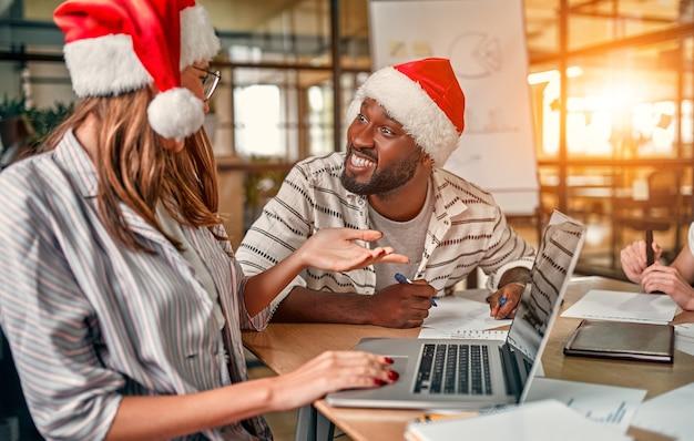 다민족 젊은 창조적 인 사람들이 현대 사무실에서 휴가를 축하하고 있습니다. 젊은 비즈니스 사람들의 그룹은 마지막 근무일에 산타 모자에 앉아 있습니다.