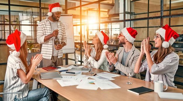 다민족 젊은 창조적 인 사람들이 현대 사무실에서 휴가를 축하하고 있습니다.