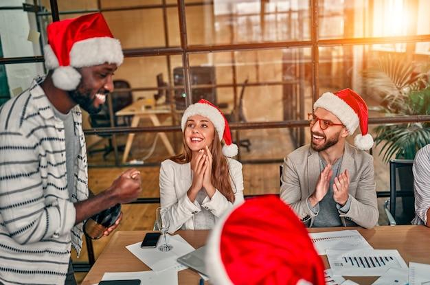 Многорасовые молодые творческие люди отмечают праздник в современном офисе.
