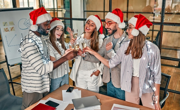 Multiracial young creative people are celebrating holiday in modern office.