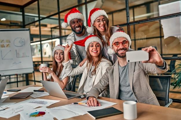 다민족의 창의적인 젊은이들이 현대적인 사무실에서 휴가를 축하하고 스마트 폰으로 셀카를 찍습니다.