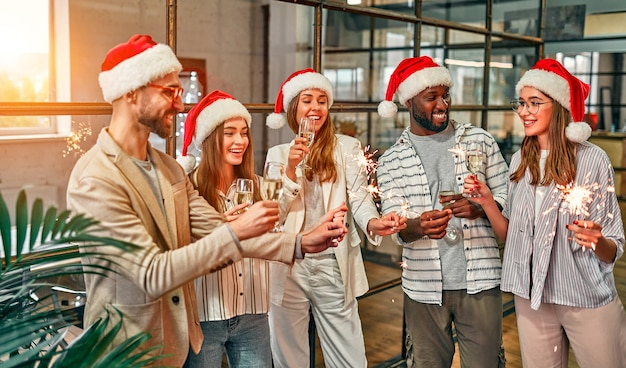 Multiracial young creative people celebrate the holiday with sparklers in a modern office. a group of young business people are drinking champagne
