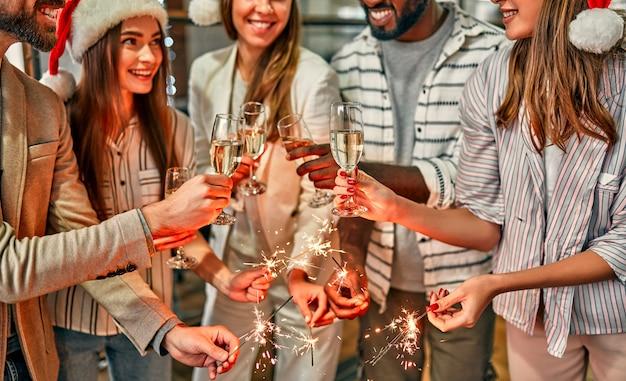 다민족 젊은 창의적인 사람들이 현대적인 사무실에서 폭죽으로 휴가를 축하합니다. 젊은 사업가 그룹 샴페인을 마시고있다