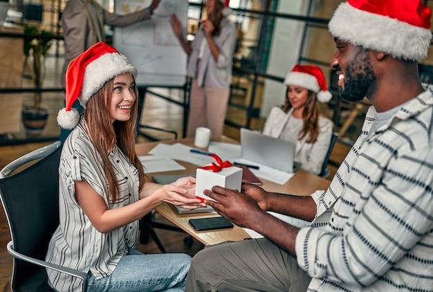 산타 모자를 쓰고 다인종 젊은 창의적인 사람들이 마지막 근무일에 동료들과 선물을 교환합니다.