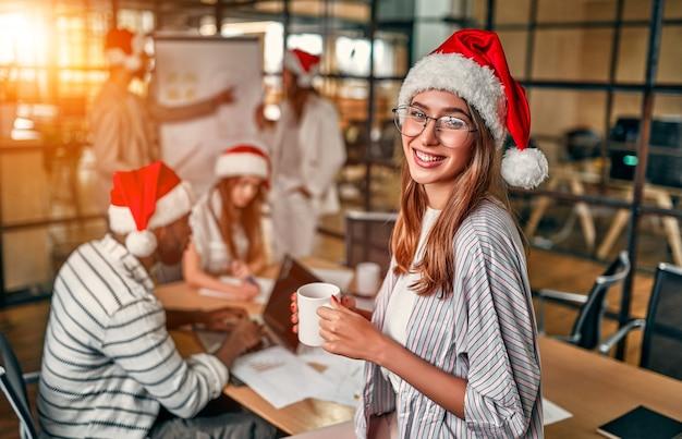 다민족 젊은 창조적 인 사람들은 산타 모자를 쓰고 현대 사무실에서 일합니다.