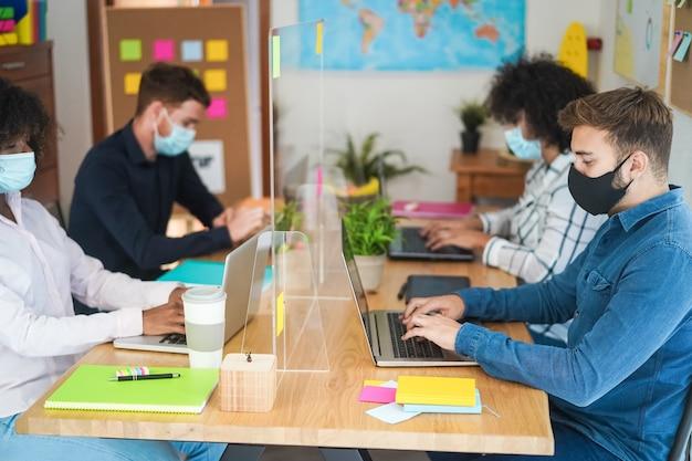 마스크를 착용하는 동안 현대 사무실에서 일하는 다민족 젊은 창조적 인 사람들-오른쪽 남자 얼굴에 초점