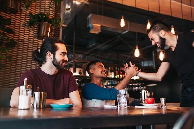Многорасовые молодые люди встречают своего друга в лаунж-баре