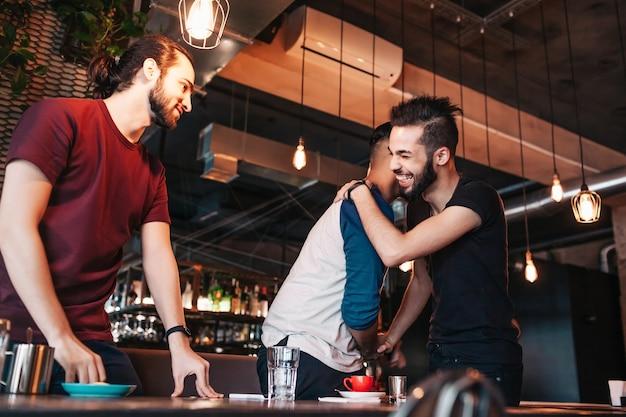 Многорасовые молодые люди встречают своего друга в лаунж-кафе