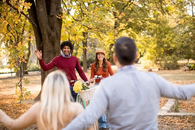 秋の公園を歩いて楽しんでいる多民族の若者