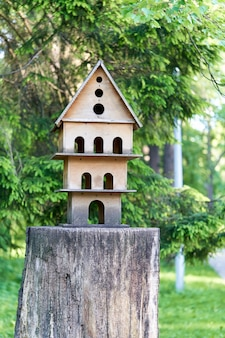 Multistorey bird house on a tree stump in the park