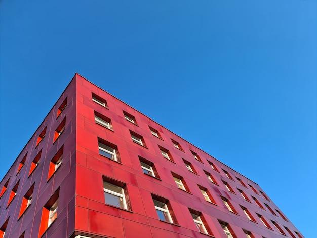 푸른 하늘 배경에 서 있는 다층 빨간 건물
