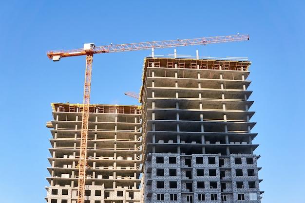 하늘에 타워 크레인으로 건설 중인 아파트의 다층 블록