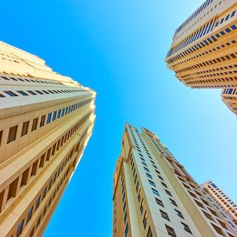 Многоэтажные жилые дома против голубого неба, дубай, оаэ