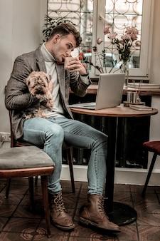 멀티 태스킹. 커피를 마시고 개를 동시에 안고 일하는 바쁜 남자