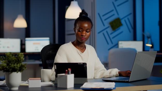 スタートアップオフィスで残業をしながらラップトップとタブレットで同時に働いているマルチタスクの黒人ビジネスウーマン。忙しいアフリカの従業員が財務統計を分析し、執筆、検索を酷使しています。