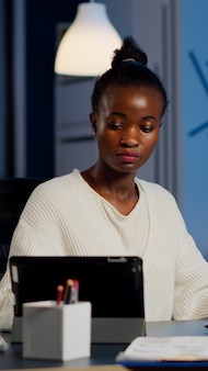 Multitasking black business woman working at laptop and tablet in same time doing overtime in start-up office. busy african employee analysing financial statistics overworking writing, searching.