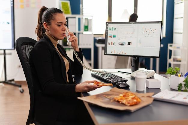Многозадачная деловая женщина разговаривает по стационарному телефону, объясняя графики компании удаленному коллеге, заказывая еду на вынос на столе. менеджер ест кусок пиццы дегустации