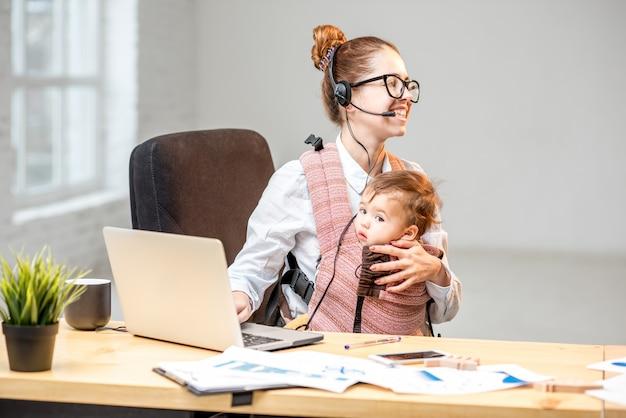 Многозадачная деловая женщина, работающая с гарнитурой и ноутбуком, сидит со своим маленьким сыном в интерьере белого офиса